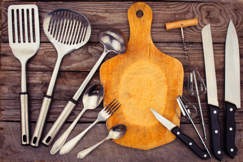 kitchen utensils on wooden background. Toned image.
